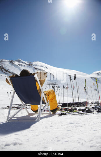 Rear view of mid adult male skier sitting on deck chair, Austria - Stock Image