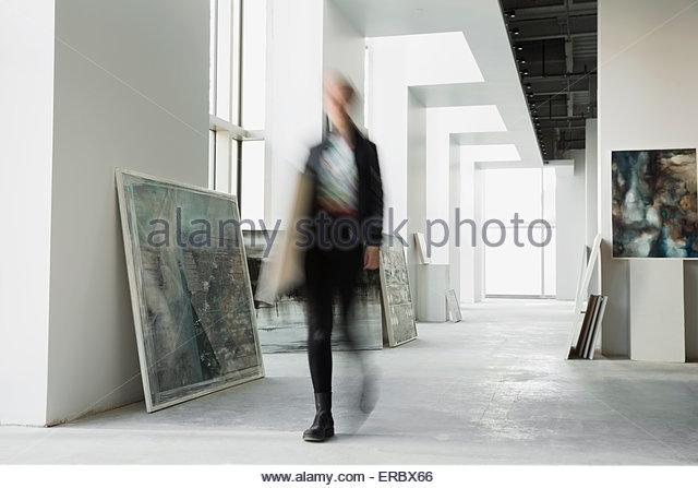 Art dealer walking with paintings in art gallery - Stock-Bilder
