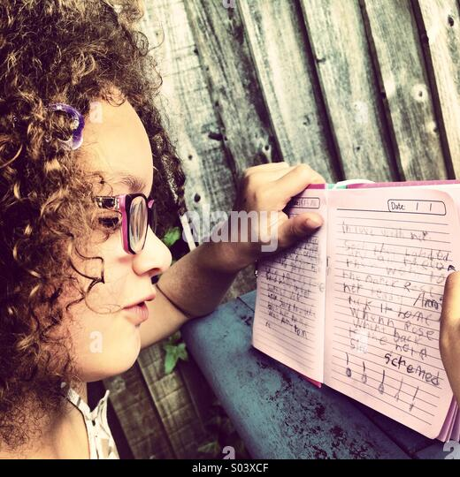Curly haired 6 year old girl wearing glasses reading her journal. - Stock Image