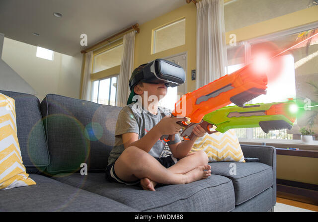 Young boy sitting cross legged on sofa, wearing virtual reality headset, holding laser guns, digital composite - Stock-Bilder