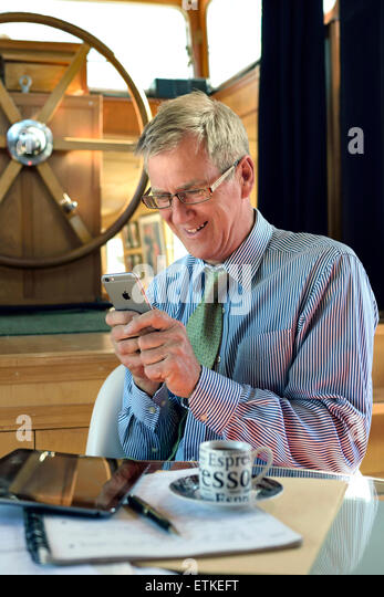 Smiling entrepreneur businessman texting with his iPhone 6 smartphone sitting in his barge houseboat office facility - Stock-Bilder