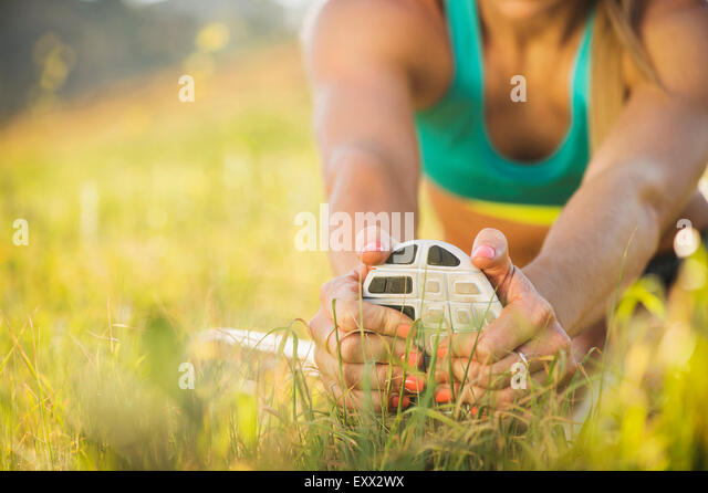 Woman exercising in field - Stock-Bilder