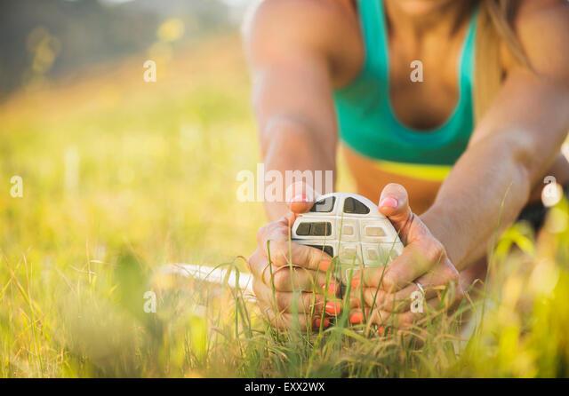 Woman exercising in field - Stock-Bilder