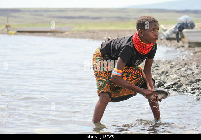 LOIYANGELENI, KENYA - May 18. A Samburu maiden washes dishes on the shores of Lake Turkana at Loyangalani. Credit: - Stock Image