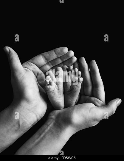 Baby's Feet In Mothers Hands - Stock Image