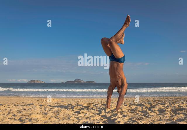 Mid adult man doing handstand on beach, Rio de Janeiro, Brazil - Stock Image