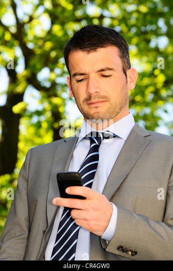 businessman is having a communication with his cellphone - Stock Image