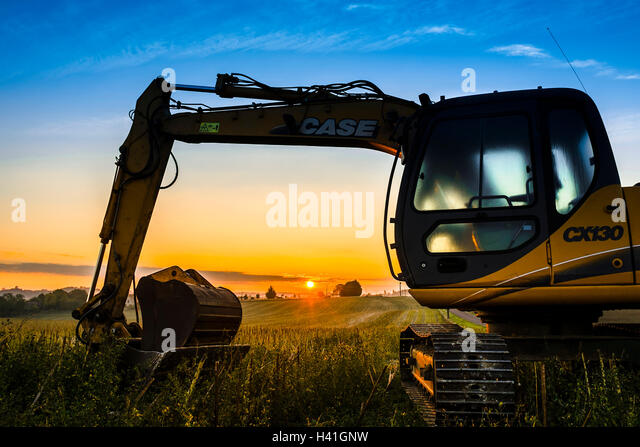 Case mechanical digger excavator at sunrise - France. - Stock Image