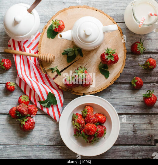 Strawberries and cream on wooden table - Stock Image