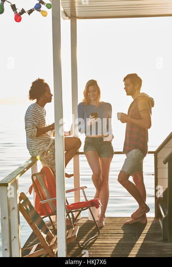 Young adult friends hanging out on sunny summer houseboat - Stock-Bilder