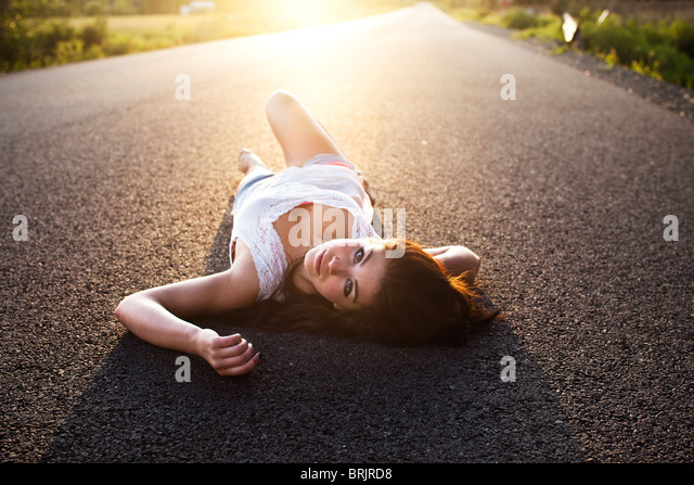A girl lies on the road at sunset in Idaho. - Stock Image