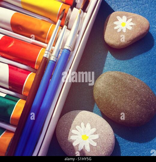 Paint tubes and brushes with pebble on blue background. Two pebbles with  drawing daisy. - Stock Image