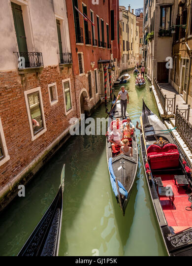 Gondolas passing each other on a narrow, congested canal in Venice, Italy. - Stock Image