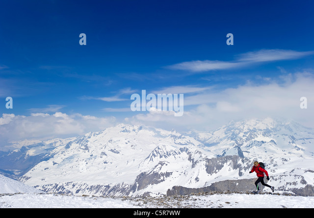 A woman running on high mountain snowy peaks. - Stock-Bilder