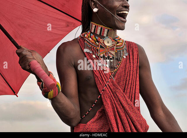 A Maasai Warrior smiles happily wearing traditional beaded tribal jewelry. Kenya, Africa. - Stock Image
