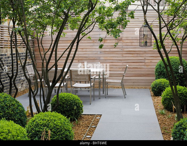 Modern table and chairs against tall wooden fence in architectural townhouse garden with clipped box shrubs and - Stock Image