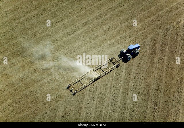 aerial above a tractor plowing a field in California Central Valley - Stock Image