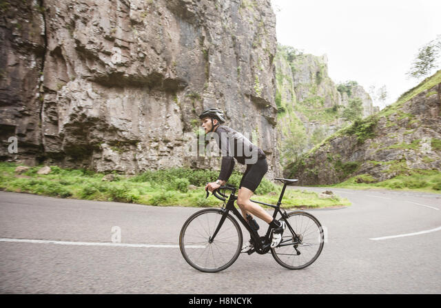 A young cyclist climbing a hill in Cheddar George - Stock-Bilder