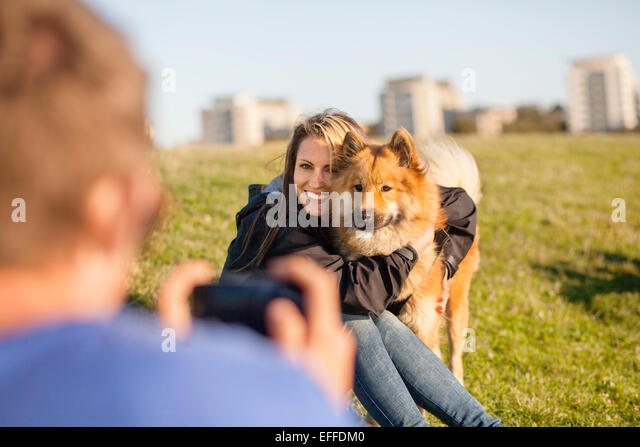 Cropped image of man photographing happy girlfriend embracing dog at park - Stock-Bilder