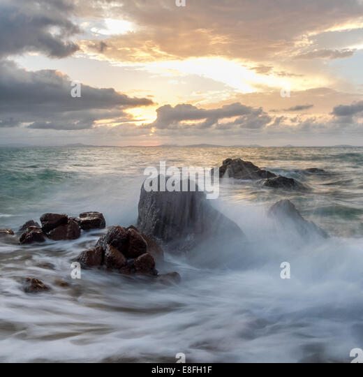 Waves crashing against rocks - Stock Image