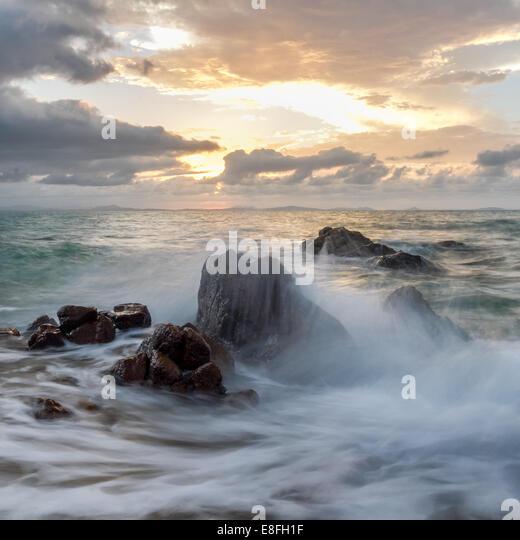 Waves crashing against rocks - Stock Image