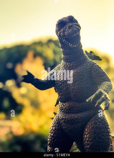 Vintage Godzilla Figure with trees in background - Stock Image
