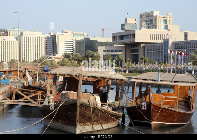 Working dhows moored at the harbour on Doha's Corniche, in Qatar, Arabia. In the background are buildings  from - Stock Image