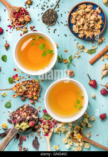 Two cups of healthy herbal tea with mint, cinnamon, dried rose and camomile flowers in spoons over blue background - Stock Image