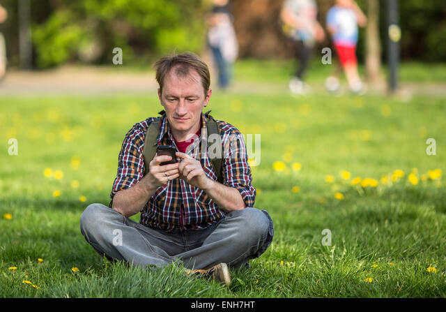 Young man with smartphone sitting on the grass in a city Park. - Stock Image