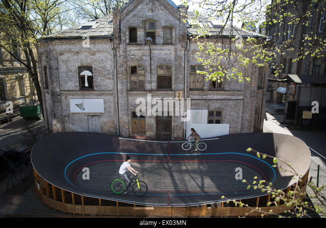 High angle view of two cyclists racing around city velodrome, Riga, Latvia - Stock Image