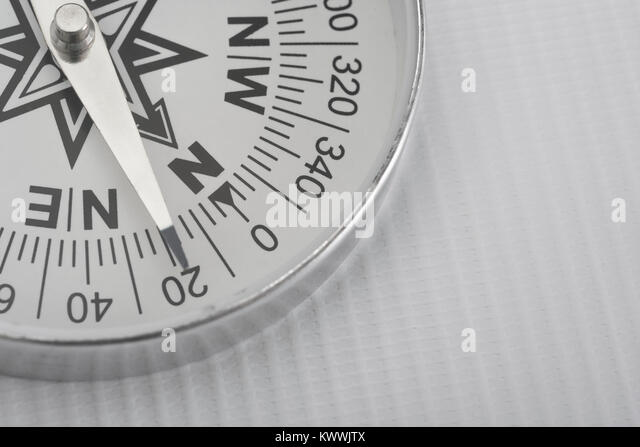 Macro-photo of compass rose face with needle. - Stock Image