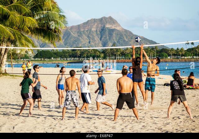 Hawaii Hawaiian Honolulu Ala Moana Beach State Regional Park volleyball game recreation sand Asian student playing - Stock Image