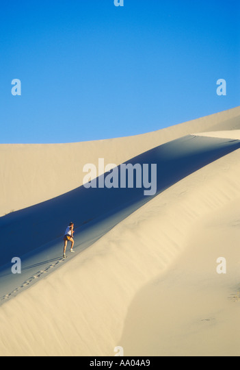 Man running on sand dunes in Death Valley California USA model released image - Stock Image
