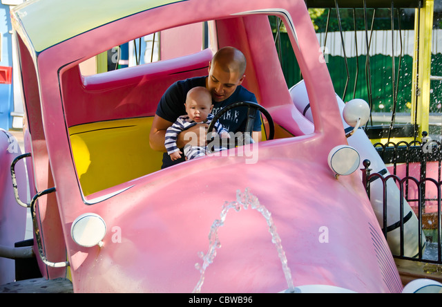 Curious George kids attraction man and baby inside pink car at Universal Studios Orlando  Florida - Stock Image