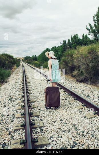 Woman walk away with a suitcase by a railway road - Stock Image