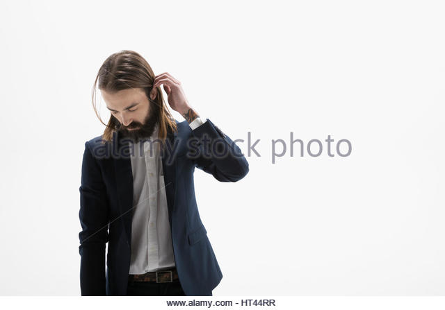 Cool businessman with beard looking down against white background - Stock-Bilder