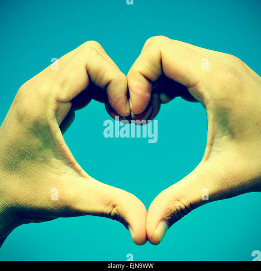picture of man hands forming a heart over the blue sky, with a retro effect - Stock Image