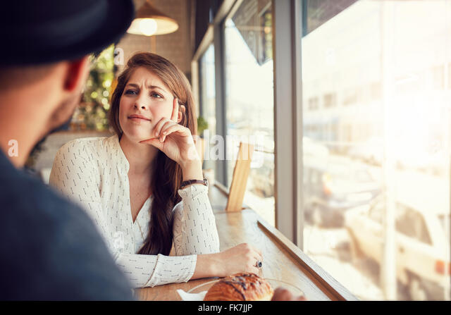 Beautiful young woman sitting in a cafe and looking at her boyfriend. Young couple at coffee shop. - Stock-Bilder