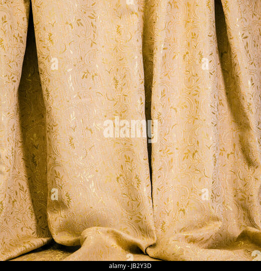 Background texture of drapes of golden damask material with a shiny self patterning of flowers and acanthus leaves - Stock Image