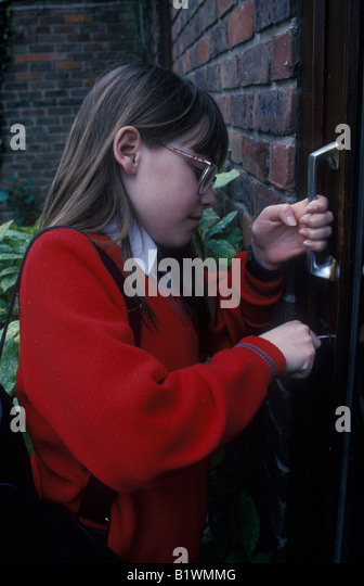 Child using key to enter her home - Stock Image
