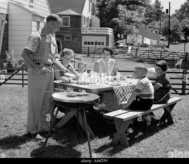 1950s FAMILY IN BACKYARD COOKING HOT DOGS SITTING AT PICNIC TABLE - Stock Image