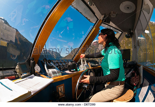 Captain Dawn Rauwolf steering the tour boat Kalinin in Misty Fjords National Monument, near Ketchikan, southeast - Stock Image