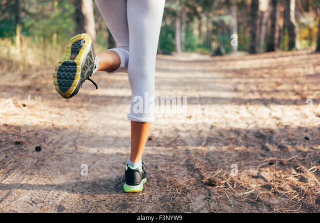 Runner feet running on road close-up on shoe. woman fitness at sunrise - Stock Image