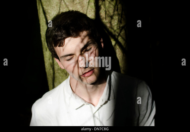Young man with shadow of tree branches in the face - Stock Image