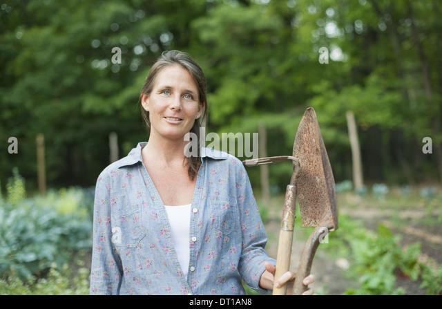 Woodstock New York USA woman working organic garden vegetable crops spade - Stock Image