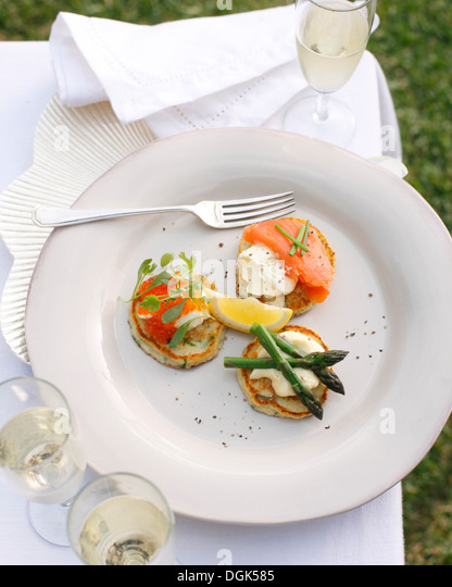 Plate of potato pancakes with creme fraiche, salmon roe and asparagus - Stock Image