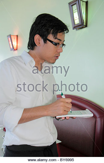 Miami Florida Biscayne Boulevard Bengal Modern Indian Cuisine restaurant Asian man waiter writing order service - Stock Image