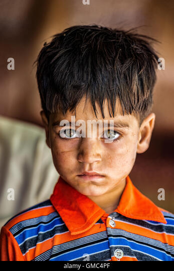 Small Pakistani boy in a tea house beside the Karakoram Highway between Gilgit and Islamabad - Stock Image