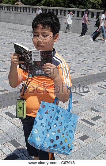 Tokyo Japan Harajuku Asian boy library book reading - Stock Image