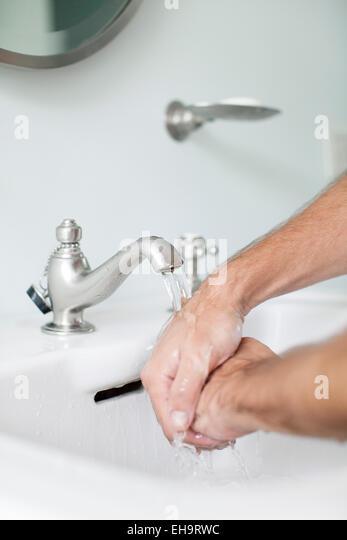 Man washing hands in bathroom sink - Stock-Bilder